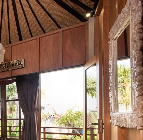 Wooden Lumbung room with wide opening windows and views East for sunrise.