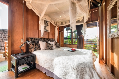 Lumbung room with QUEEN bed, draped netting, wooden lined and traditional BEDEG woven ceiling Plus wide opening windows onto your private veranda.
